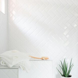 An inexpensive alternative to more pricey tiles simple subway tiles were installed in a herringbone pattern in the shower. White grout between the tiles lends a more cohesive look.